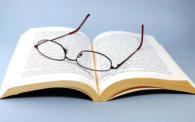 Жапон көзілдірігі кітапты оқу үстінде аударады