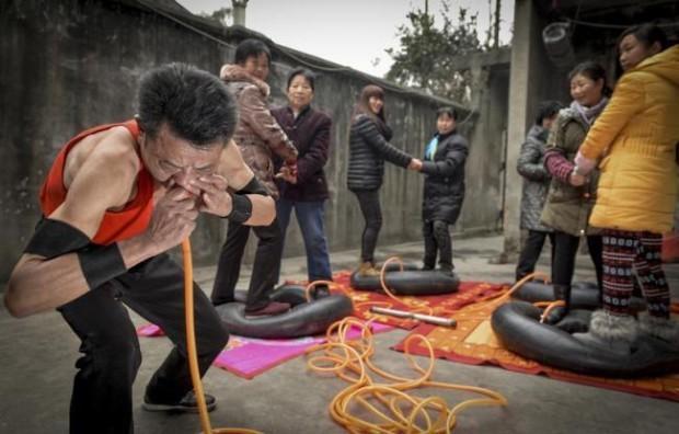 Автокөлік шинасын мұрнымен үрлейтін Ни Йонгбинг